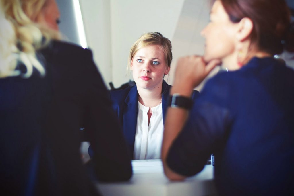 Three women in business attire sitting together