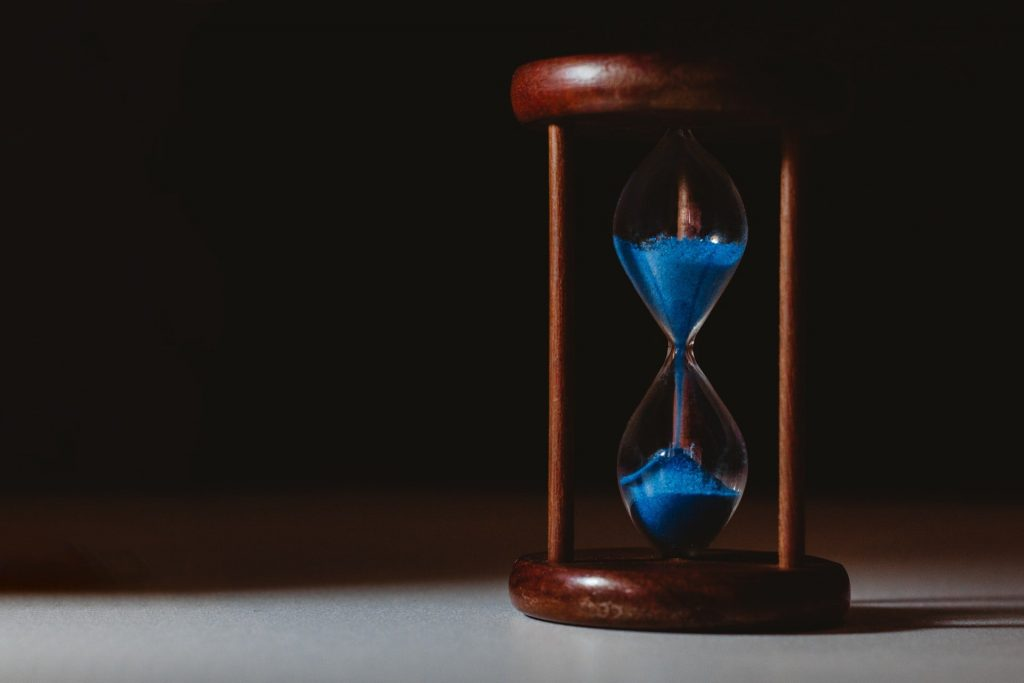 An hourglass containing blue sand