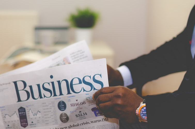 Man holding the business section of the newspaper