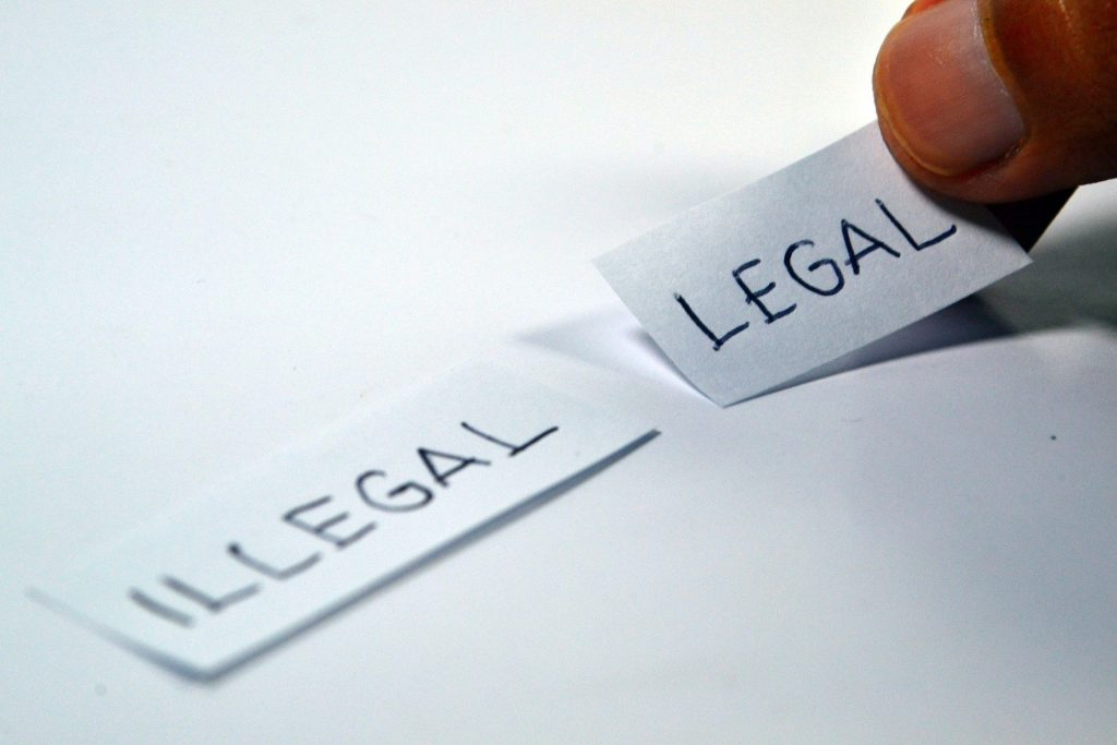 Words legal and illegal written in separate papers