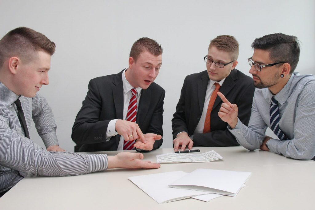 Four businessmen debating at a table