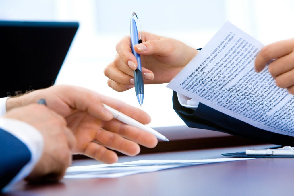 2 men signing legal papers