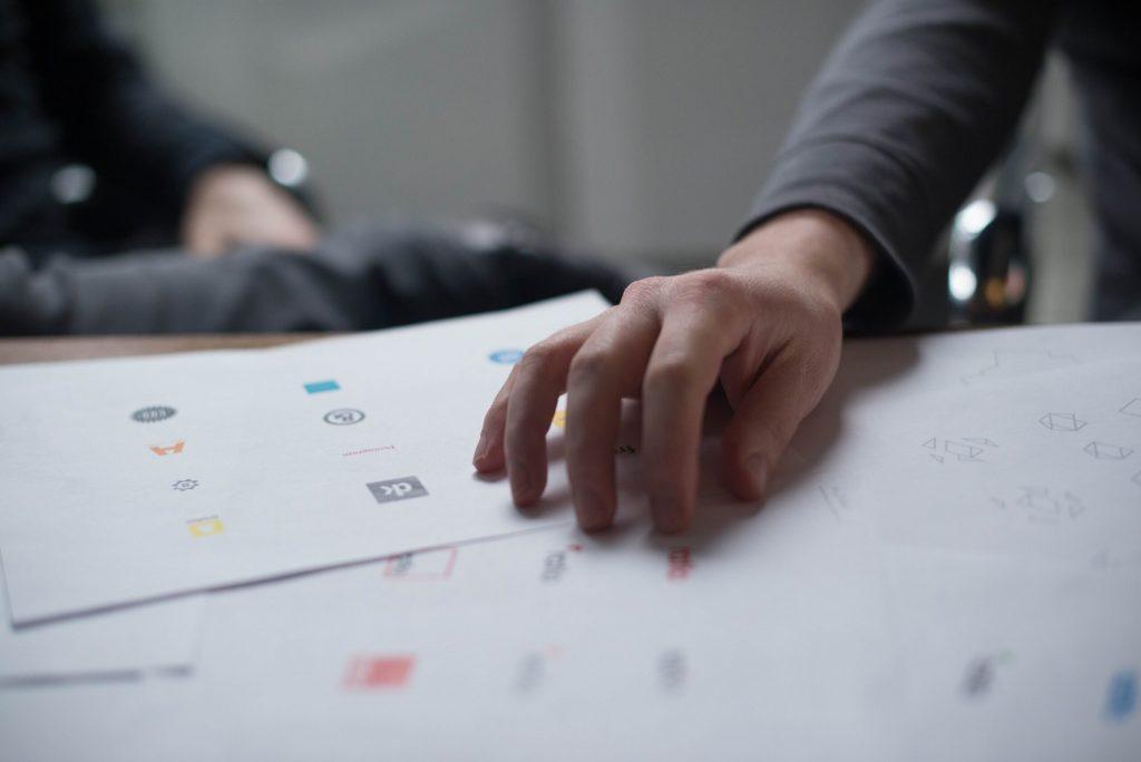 Man looking through various logo designs