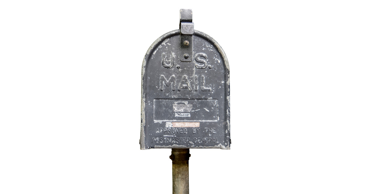 Beat up post box against a white background